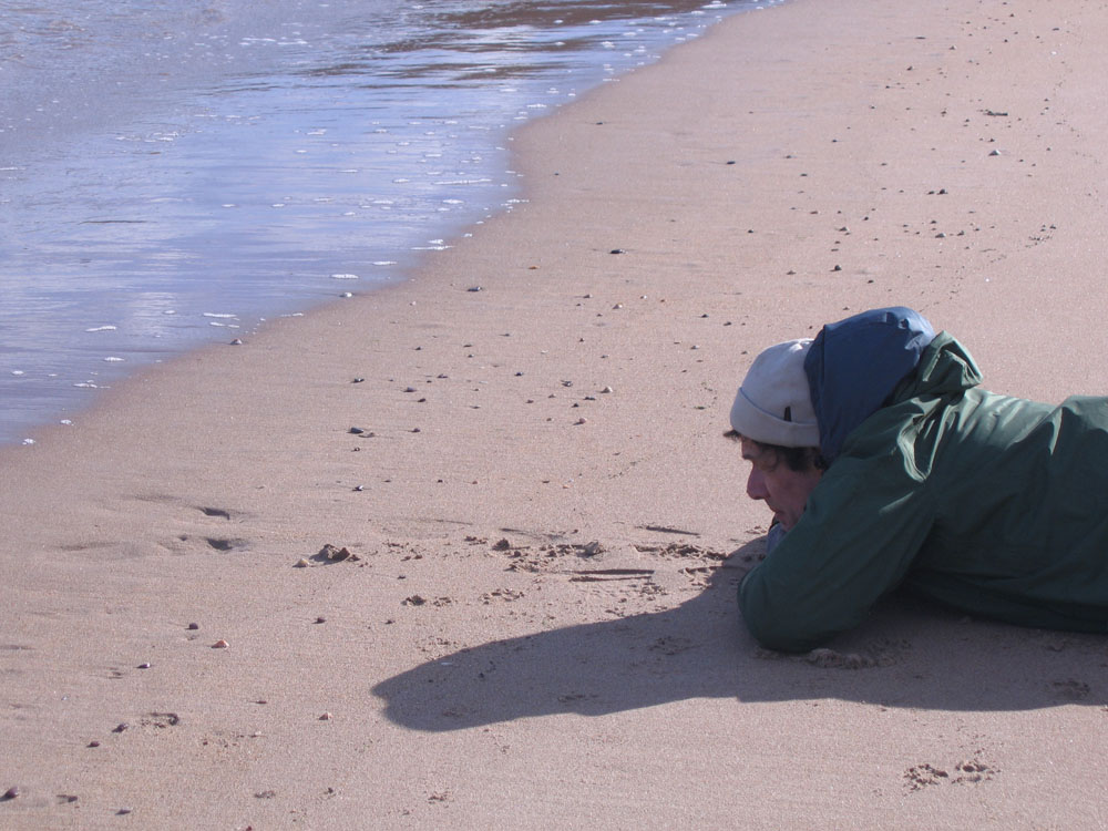 photo of man lying by the sea