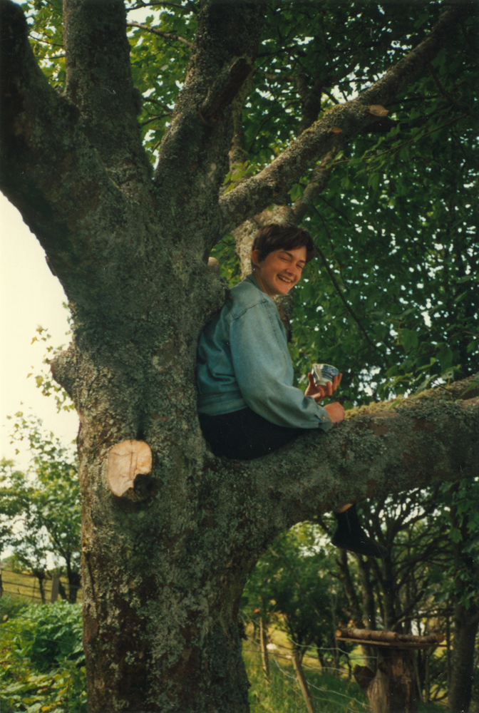a photograph of my sister sitting in a tree drinking tea