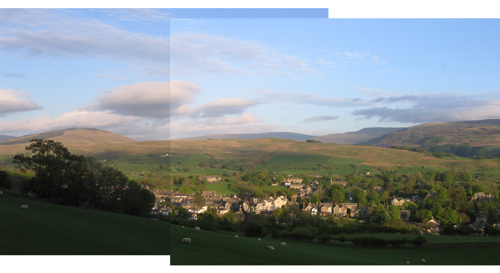photo of the view from Winder - Sedbergh nestling in the hills, blue sky, evening colours of green, gold and violet