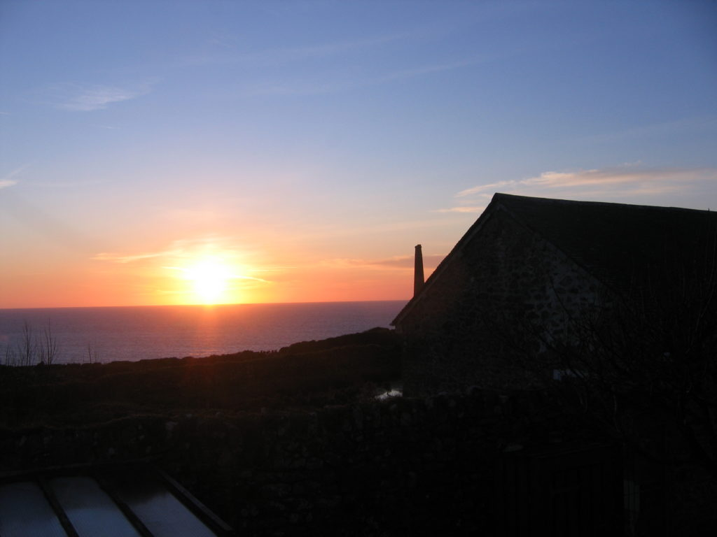 photo of sun setting into the sea as seen from the garden of a cottage in Cornwall