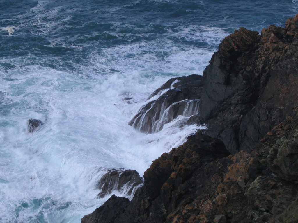 A photo of waves crashing into cliffs