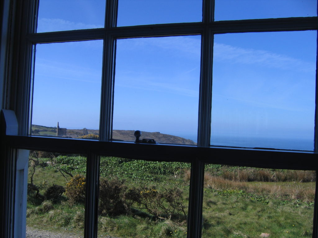 Blue sky and sea, green grass as seen through a window, colour photo, Cornwall