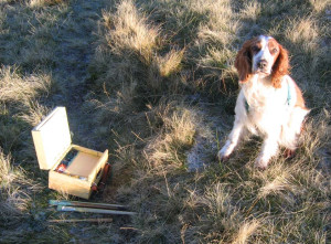 dog sitting beside painter's box
