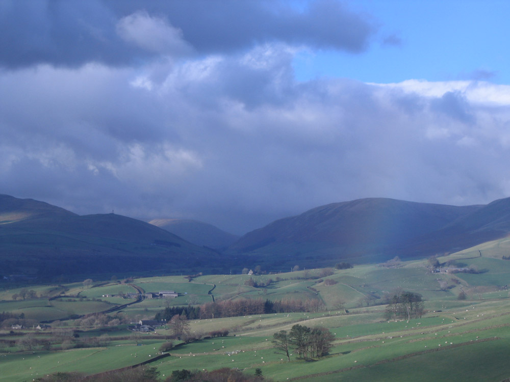 photo of rainbow and dark hills