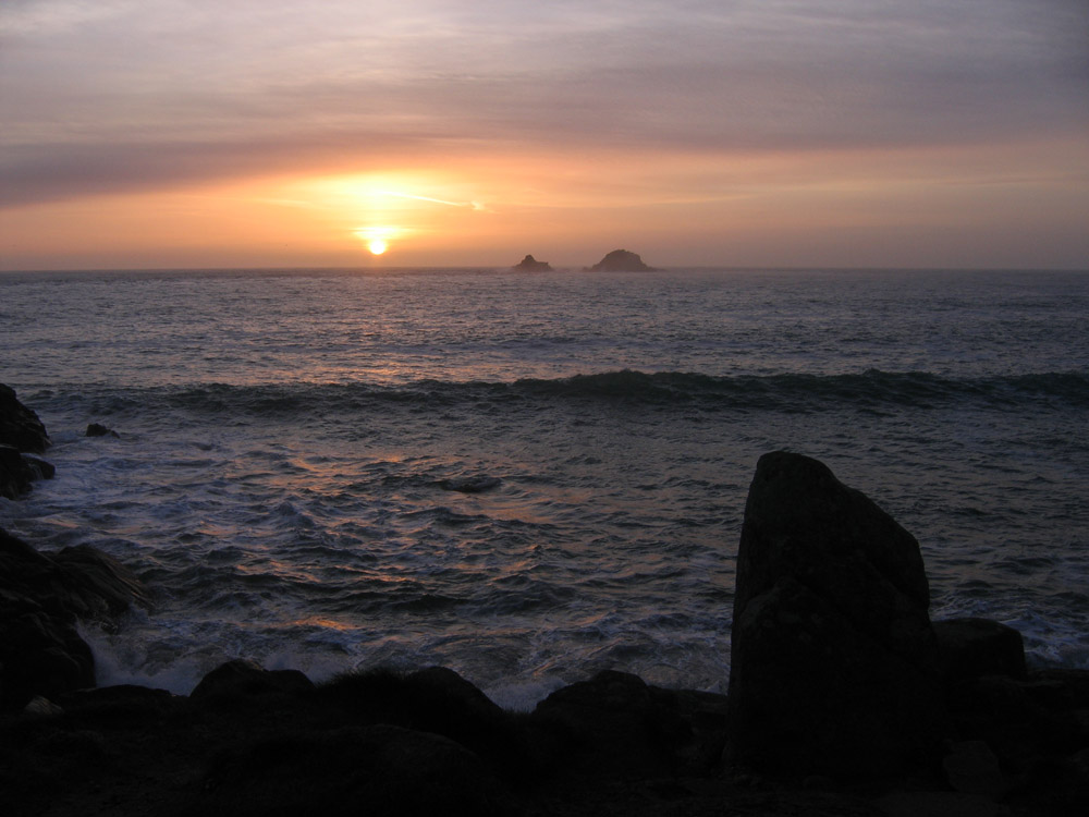 setting sun over the sea with distant Brisons, Cornwall